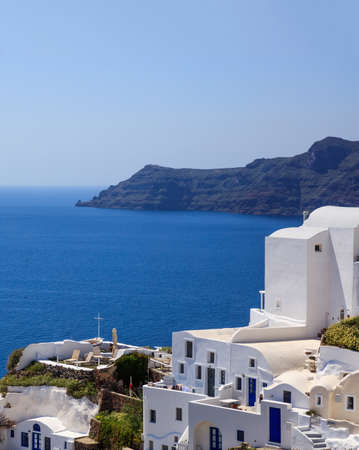 Santorini island, Greece. Oia caldera over Aegean sea, blue clear sky, calm sea 免版税图像