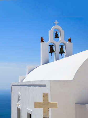Santorini island, Greece. White orthodox church and bells back side view, against blue sea and clear sky background over caldera, vertical photo