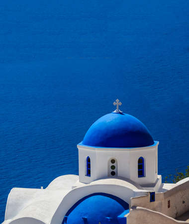 Santorini island, Greece. White orthodox church with blue dome against blue calm sea background, Oia village 免版税图像