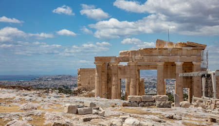 Athens Acropolis, Greece landmark. Propylaea entrance gate and Athens city view from above, blue cloudy sky in spring sunny day.