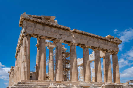 Athens Acropolis, Greece. Parthenon temple facade, ancient temple ruins, equipment for restoration works, blue sky, low angle view