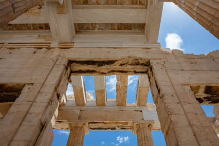 Athens Acropolis, Greece landmark. Ancient Greek Propylaea entrance gate ceiling and columns low angle view, blue sky, spring sunny day.
