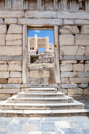 Athens Acropolis, Greece landmark. Entering Propylaea, Ancient Greek entrance gate to Acropolis, view from a marble opening, vertical photo