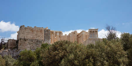 Athens, Greece. Acropolis rock and Propylaea gate, view from Areopagus hill, blue cloudy sky, spring day