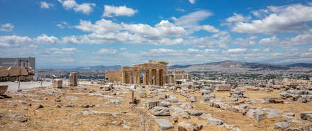 Athens Acropolis, Greece landmark. Propylaea entrance gate, Ancient Greek ruins and panoramic view of Athens city, blue cloudy sky background.