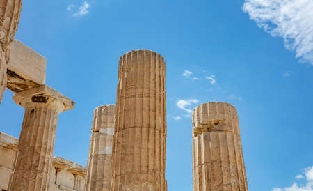 Athens Acropolis, Greece landmark. Ancient Greek columns pillars at Propylaea entrance gate closeup view blue sky, sunny spring day.