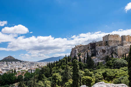 Athens, Greece. Acropolis rock, Mount Lycabettus and city view from Areopagus hill, blue cloudy sky, spring day