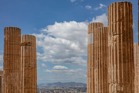 Athens Acropolis, Greece landmark. Ancient Greek columns pillars at Propylaea entrance gate closeup, city view and blue cloudy sky.