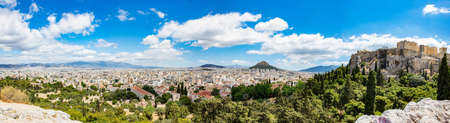 Athens, Greece panoramic view from Areopagus hill. Acropolis rock, Mount Lycabettus and cityscape view, blue cloudy sky, spring day