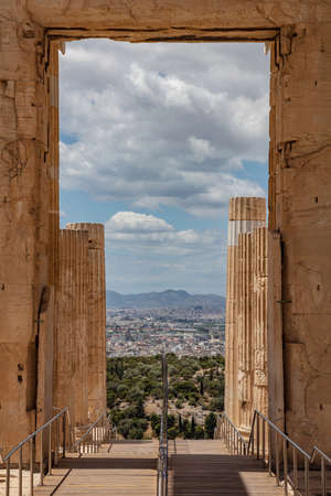 Athens Acropolis, Greece landmark. Leaving Ancient Greek Propylaea, city view from an opening with ionic style pillars, vertical photo, blue cloudy sky