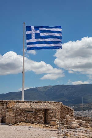 Athens Acropolis, Greece. Greek flag waving on pole, against blue sky background, spring sunny day, vertical photo. 免版税图像