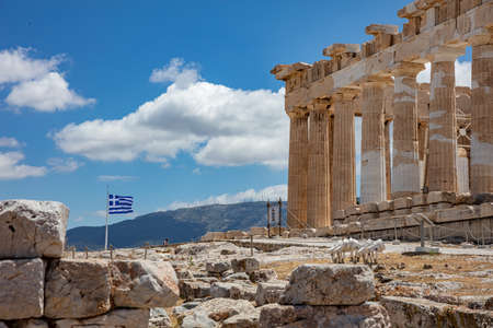Athens Acropolis, Greece. Parthenon temple and greek flag waving against blue sky background, spring sunny day.
