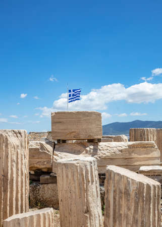 Athens Acropolis, Greece. Greek flag waving on pole, ancient column remains against blue sky background, spring sunny day.