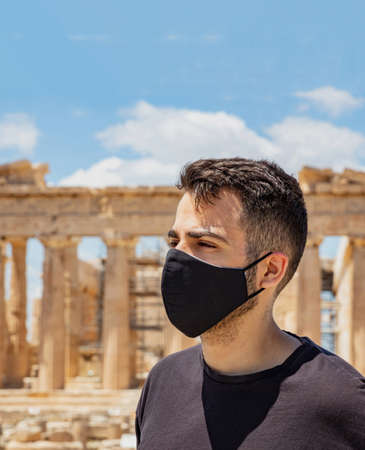 Athens Acropolis, Greece coronavirus days. Young man wearing protective face mask, Ancient Greek Parthenon temple and blue sky background.