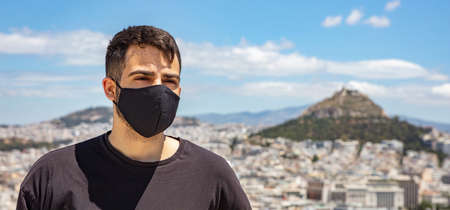 Athens Greece coronavirus days. Young man wearing protective face mask, Athens city scape with Lycabettus mount and blue sky background.