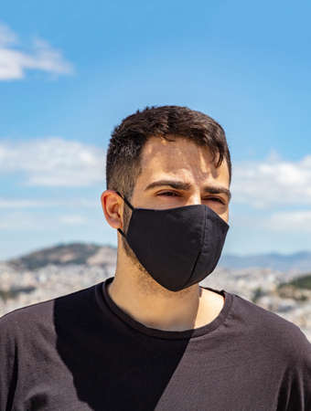Athens Greece coronavirus days. Young man wearing protective face mask, Athens cityscape and blue sky background.