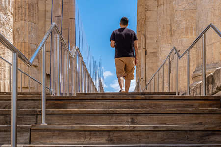 Athens Acropolis, Greece landmark. Young man back view walking alone on wood deck and stairs, Ancient Greek Propylaea, protective partitions measures for coronavirus days