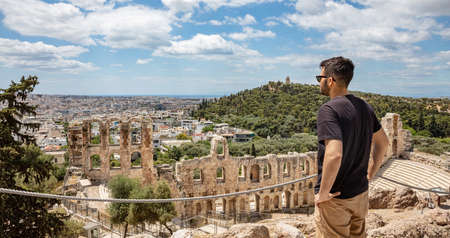 Herodes Atticus Odeon, Herodium, ancient theater under Acropolis, Greece. Young man looking at the Athens city view over the theatre, sunny spring day, blue sky