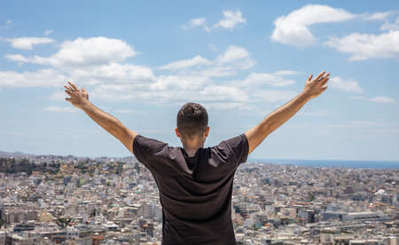 Man back with raised arms. Young adult rear view standing alone with open hands looking at the city below, blue sky background. Healthy lifestyle, freedom, success concept 免版税图像