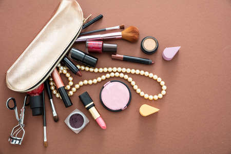 Make up cosmetic bag with professional accessories. Lipsticks and brushes out of a gold cosmetic bag against brown color background, copy space. 免版税图像