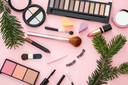 Makeup xmas flat lay background. Lipstick and eye shadows blush, brushes and christmas decoration against pink color background. New year eve party make up concept 免版税图像 - 148512749