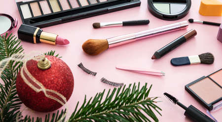 Makeup xmas flat lay background. Lipstick and eye shadows blush, brushes and christmas decoration against pink color background. New year eve party make up concept