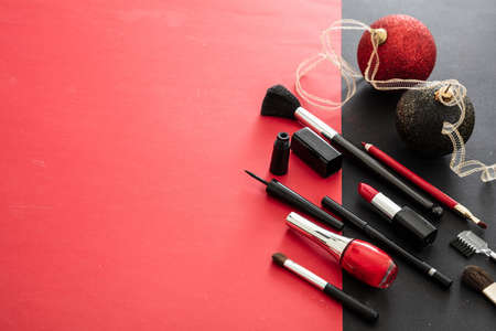 Makeup xmas party concept, red and black flat lay background. Make up products and christmas balls, New years eve preparation