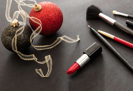 Makeup xmas party concept. Make up products and christmas balls red and black against black background. New years eve preparation