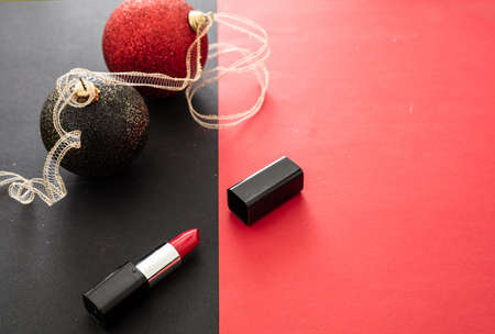Red lipstick, xmas, new years eve makeup. Red vibrant color lipstick and christmas balls, copy space, top view