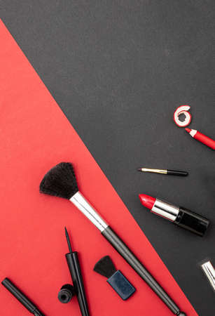 Make up cosmetics accessories in red and black. Lipstick, nail polish, eye pencil and brushes against red and black color background 免版税图像
