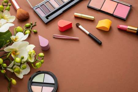 Makeup natural cosmetic products against brown color background. Make up female accessories, flat lay, top view, copy space