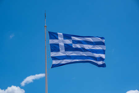 Greece sign symbol. Greek flag on flagpole waving in the wind. Blue sky, sunny spring day in Athens.