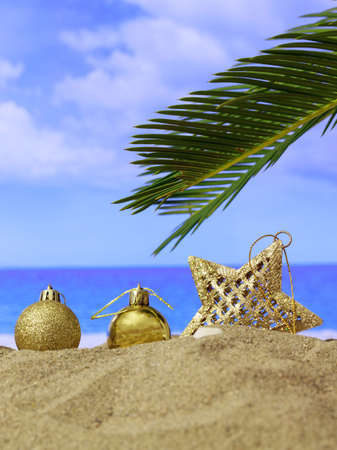 Xmas summer holidays concept. Christmas ornaments on a sandy beach with palm tree, blue sky and sea background. Vertical photo Stock Photo