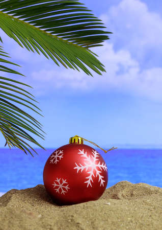 Xmas summer holidays concept. Christmas bauble on a sandy beach with palm tree, blue sky and sea background. Vertical photo Stock Photo