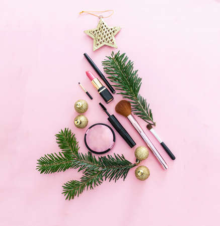 Make up xmas party concept. Professional cosmetic products in christmas tree shape against pink color background, new year eve preparation 免版税图像