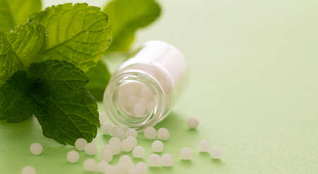 Homeopathy, globules scattered out of glass bottle and fresh mint leaves, green background. Natural alternative medicine, copy space