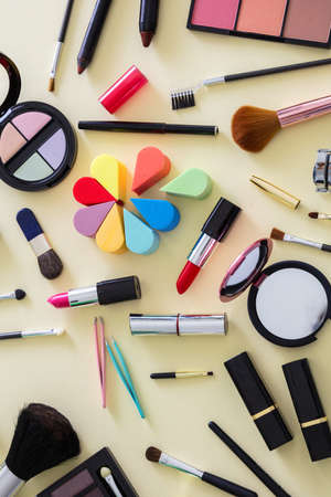 Make up cosmetics flat lay. Lipstick and nail polish, eye shadows and blush, brushes and pencils against yellow color background, top view