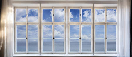 View of calm sea and blue sky background through old window concept. Vintage white window pane with frame, transparent glasses, handles and sill. Banner.