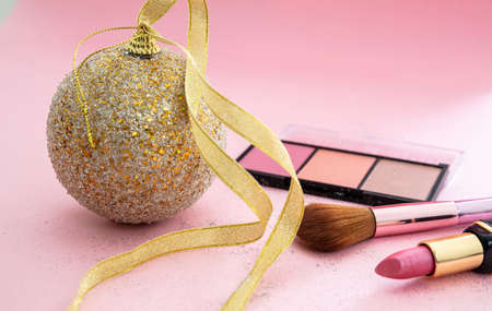 Make up xmas party concept. Professional cosmetic products top view against pink color background, Christmas, new year eve preparation