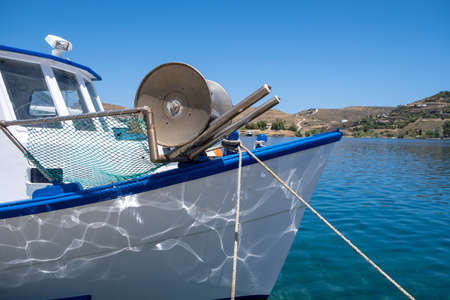 Fishing boat detail with winch and fishnet moored inTzia island, Greece. Blue sky, calm sea, sun and relaxation. Summer holidays at greek islands.