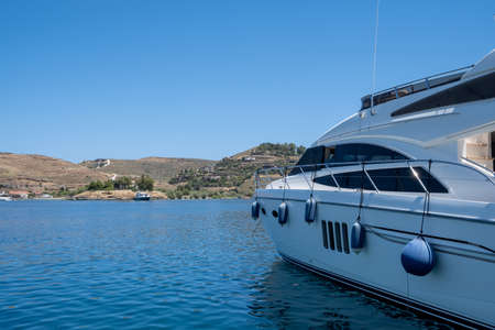 Luxury yacht with fenders moored inTzia island, Greece, closeup view.  Blue sky, calm sea, sun and relaxation. Greek islands, summer holidays destination