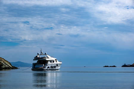 Kea, Otzias, Greece. Luxury white color yacht anchored near the land of Tzia island in the middle of the blue calm sea. Reflection of the ship, cloudy sky background.