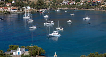 Kea island, Tzia, Greece. Many luxury white color yachts, boats anchored at Otzias bay in the middle of blue calm sea. Village, nature, sandy beach background. 免版税图像