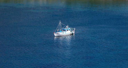 Tzia, Kea, Greece. Blue and white traditional fishing boat, trawler moored in the middle of calm sea at Otzias cove a sunny day.