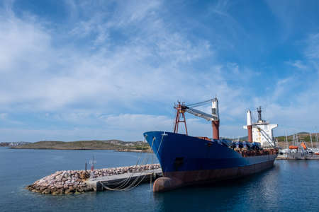 Old oil tanker moored at harbor. Ships anchored at port, city of Laurium blue calm sea and cloudy sky background. Attica, Greece. 免版税图像 - 150192732