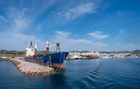 Old oil tanker moored at harbor. Ships anchored at port, city of Laurium blue calm sea and cloudy sky background. Attica, Greece. 免版税图像