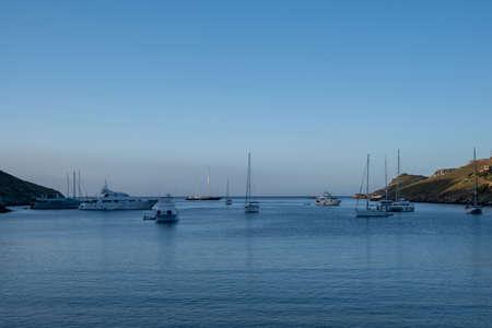 Kea, Otzias bay, Greece. Luxury yachts and sailing boats anchored inTzia island blue calm sea. Afternoon sky background. 免版税图像
