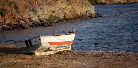 Old, empty and rusty fishing boat abandoned on the sand. Blur rocks and sea background. 免版税图像 - 150192354
