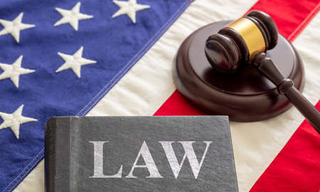 Law text on black book and judge gavel on US of America flag background. Justice in USA concept 免版税图像