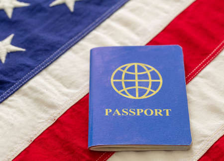 Blue passport on USA flag background, closeup view. Immigration, United States of America visa concept